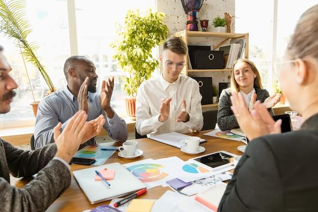 会議、創造的なオフィスを持っている若いビジネス専門家のグループ