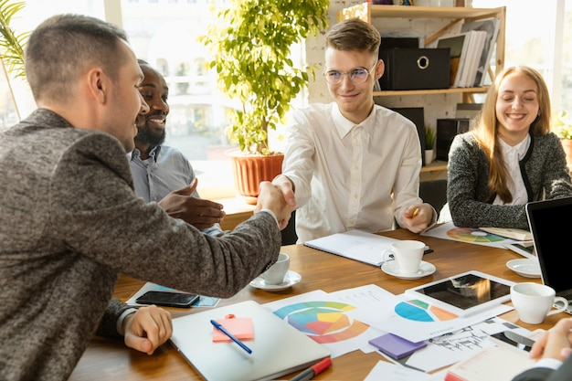 Группа молодых бизнес-профессионалов, встречающих творческий офис