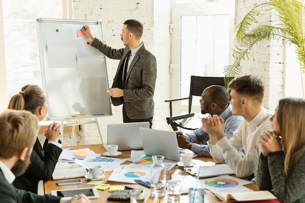ミーティングクリエイティブオフィスを持つ若いビジネス専門家のグループ