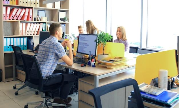 회의를 하는 젊은 비즈니스 전문가 그룹입니다. 사무실에서 회의를 하는 동안 웃고 있는 다양한 젊은 디자이너 그룹.