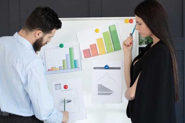 近代的なオフィスで一緒に仕事を議論する若いビジネスチームのグループ。