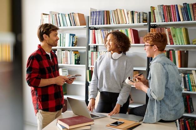 図書館でプロジェクトを準備しているときに自分のアイデアを議論する若いカジュアルな同級生のグループ