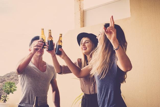 Группа молодых кавказских друзей, жарящих вместе с пивными бутылками
