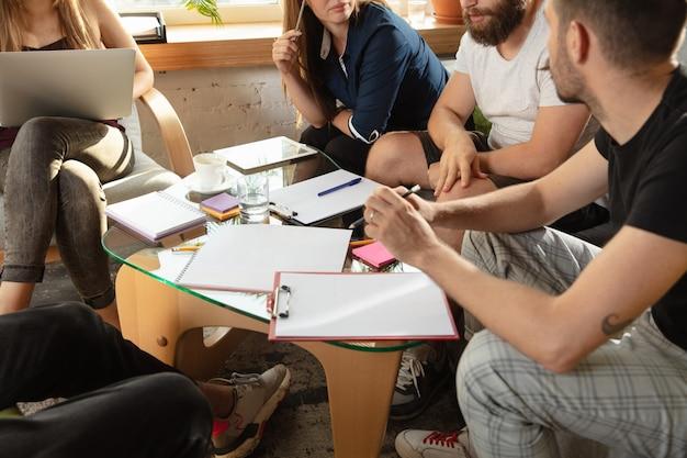 若い白人のサラリーマンのグループは、新しいアイデアを議論するために創造的な会議を持っています