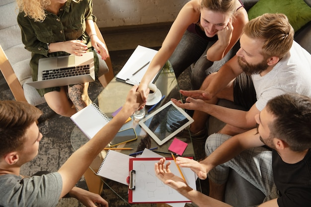 새로운 아이디어를 논의하기 위해 만나는 젊은 백인 회사원 그룹. 창의적인 만남. 팀워크와 브레인스토밍. 남성과 여성은 사무실에서 만나 미래의 일을 계획합니다. 비즈니스 개념입니다.