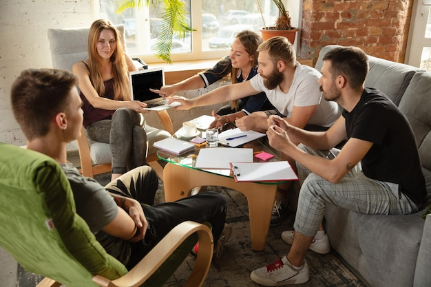 새로운 아이디어를 논의하기 위해 만나는 젊은 백인 회사원 그룹. 창의적인 만남. 팀워크와 브레인스토밍. 남자와 여자는 사무실에서 만나 미래의 일을 계획합니다. 비즈니스 개념입니다.