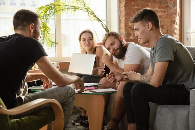 Группа молодых кавказских офисных работников, встречающихся для обсуждения новых идей. творческая встреча. работа в команде и мозговой штурм. мужчины и женщины встречаются в офисе, чтобы спланировать свою будущую работу. бизнес-концепция.