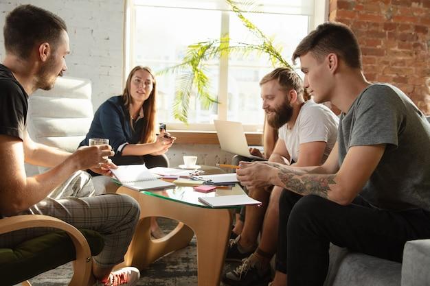 新しいアイデアを議論するために集まる若い白人サラリーマンのグループ。クリエイティブミーティング。チームワークとブレーンストーミング。男性と女性がオフィスで集まり、将来の仕事を計画します。ビジネスコンセプト。