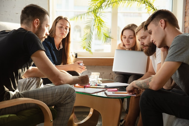Группа молодых кавказских офисных работников, встречающихся для обсуждения новых идей