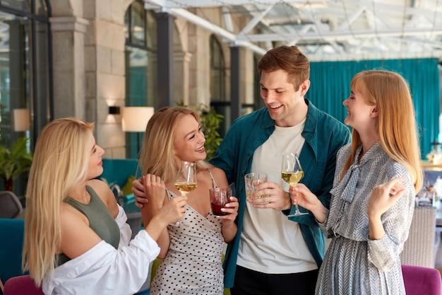 음료의 부딪 치는 유리와 함께 생일을 축하하는 젊은 백인 사람들의 그룹