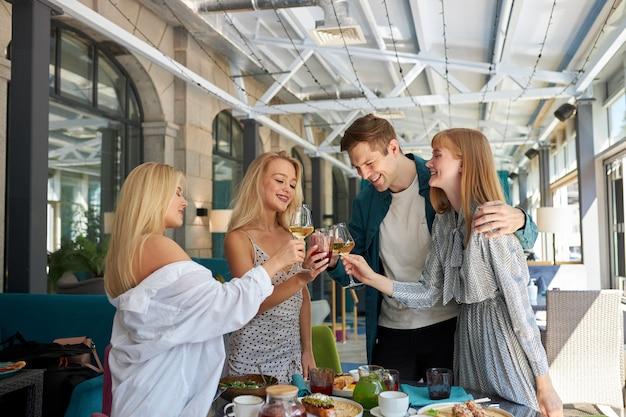 飲み物のチャリンという音で誕生日を祝う若い白人の人々のグループ