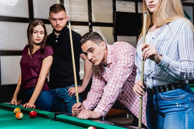 Группа молодых веселых друзей, играющих в бильярд.