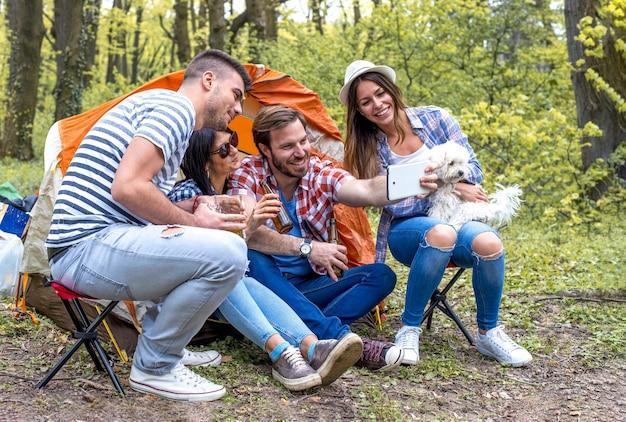 ピクニックをしながら写真の自分撮りを撮る若い陽気な友人のグループ