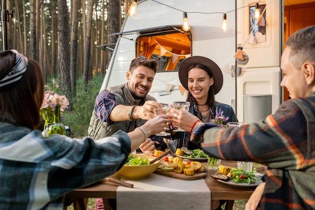와인과 함께 건배하는 젊은 쾌활한 친구의 그룹