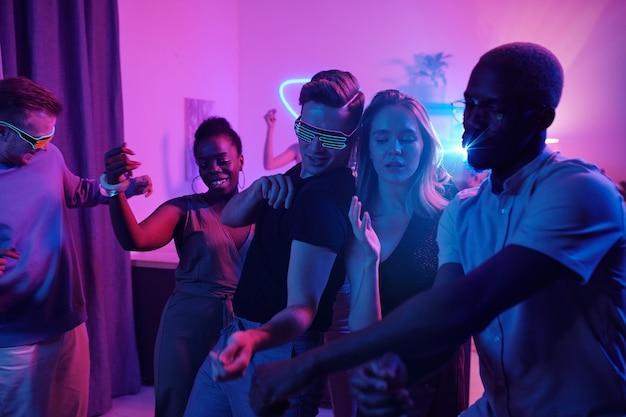 ピンクの照明で照らされたリビングルームでホームパーティーで興奮して踊るスマートカジュアルウェアの若い陽気な異文化の友人のグループ