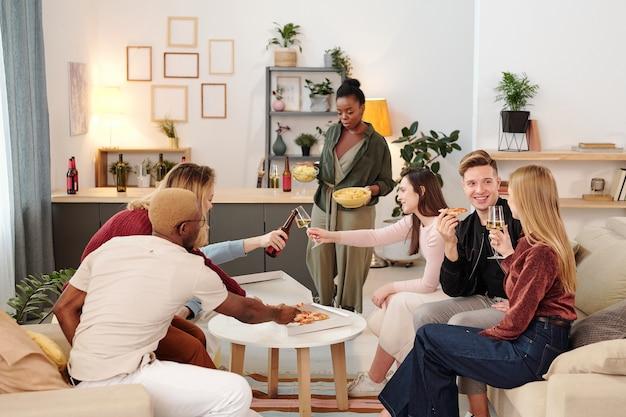 リビングルームの小さな白い円卓のそばに座って、ピザと飲み物を持っているスマートカジュアルウェアの若い陽気な異文化の友人のグループ