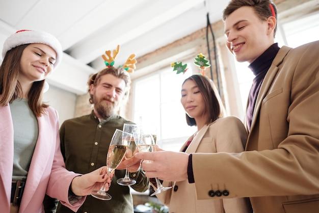 크리스마스 날 샴페인 피리와 부딪치는 똑똑한 캐주얼웨어와 크리스마스 머리띠를 입은 젊은 쾌활한 관리자 그룹