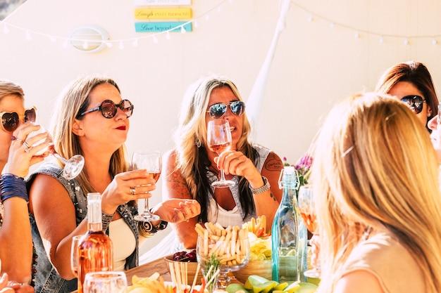 若い陽気な女性のグループは、自宅やレストランで昼食時に一緒に楽しんでいます