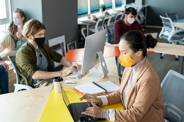 Группа молодых сотрудников в повседневной одежде и защитных масках, сидящих в офисе на открытом воздухе и использующих мобильные устройства во время индивидуальной работы