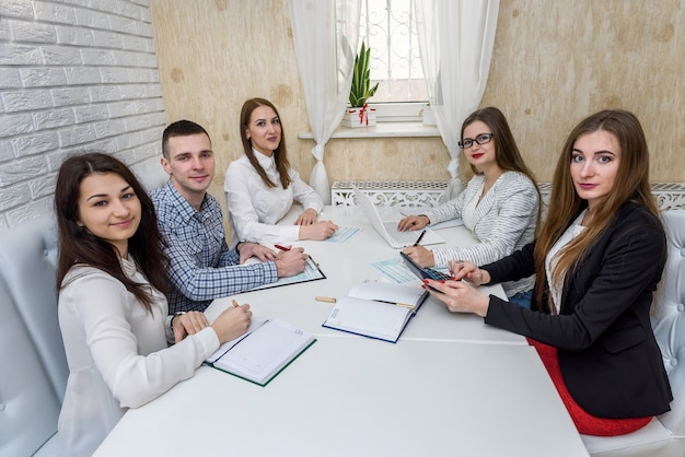 1040税務フォームを指しているオフィスの若いコンサルタントのグループ