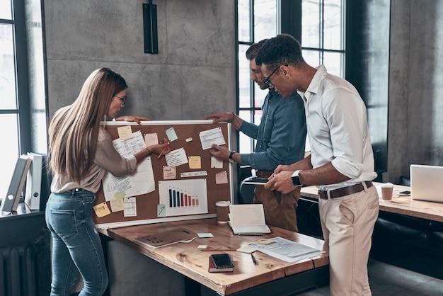 사무실에서 일하는 동안 비즈니스에 대해 토론하는 스마트 캐주얼 복장을 한 젊은 동료 그룹