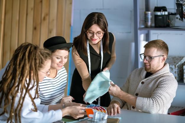 Группа молодых дизайнеров обсуждает образец текстиля во время работы над новой модной коллекцией в студии