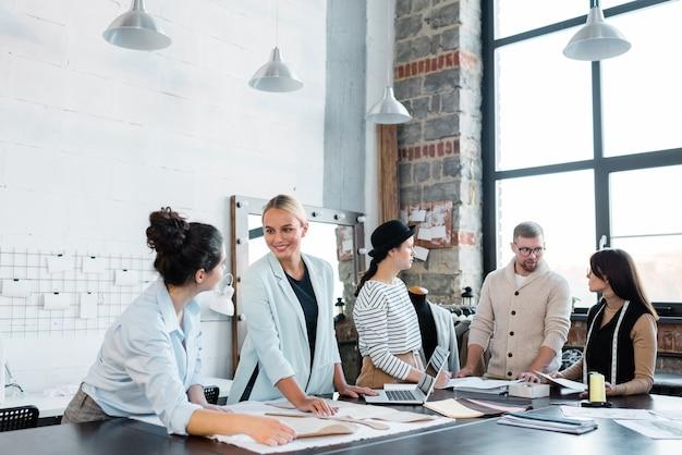 Группа молодых дизайнеров стоит за столом и обсуждает процесс шитья в лофт-студии