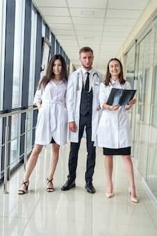 젊은 의사 그룹에 대해 논의하고 병원에서 엑스레이 스캔 다리를 찾고 있습니다. 팀 의료 업무의 개념