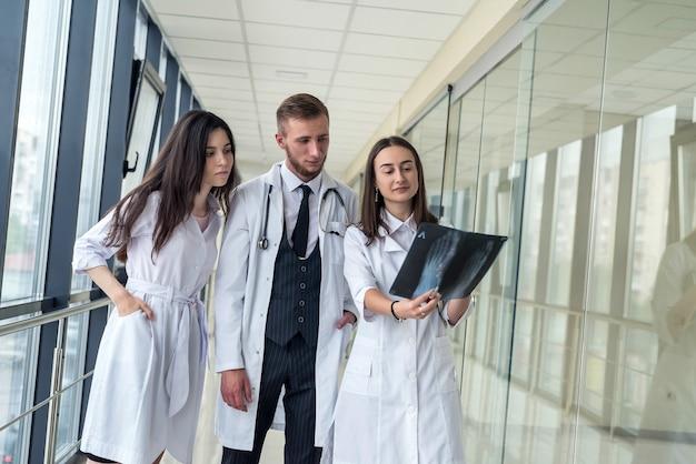젊은 의사 그룹이 클리닉에서 엑스레이 스캔 다리를 토론하고 보고 있습니다. 팀 의료 작업의 개념