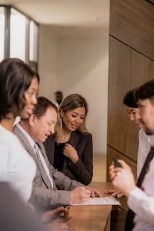 Группа молодых элегантных бизнесменов разных национальностей, стоящих у стойки регистрации в холле отеля