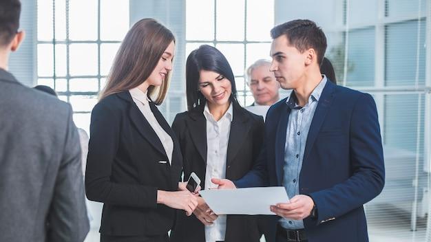 休憩中にオフィスのロビーに立っている若い従業員のグループ。オフィス就業日