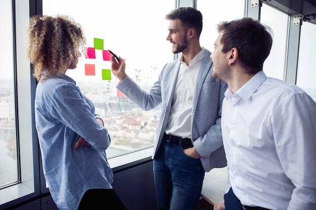 若い起業家のグループは、オフィスでの作業プロセス中にビジネスソリューションを探しています。コンセプトを満たすビジネスマン。