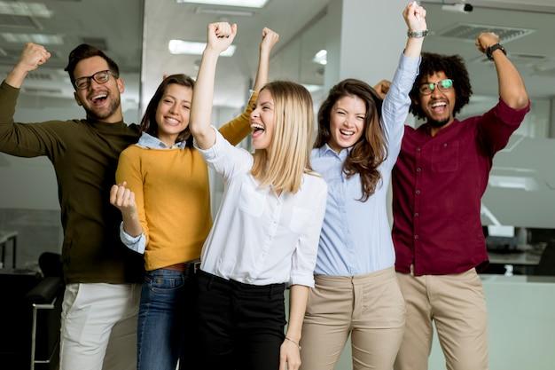 사무실에 서서 위로 손으로 젊은 흥분된 사업 사람들의 그룹