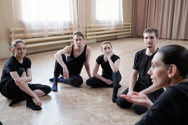 床に座ってスタジオダンスのインストラクターの話を聞いている黒いアクティブウェアの若いフィットの男性と女性のグループ