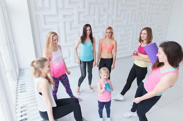스튜디오에서 피트니스 또는 댄스 수업을 마친 후 어린 소녀와 채팅을 하는 젊은 여성 그룹