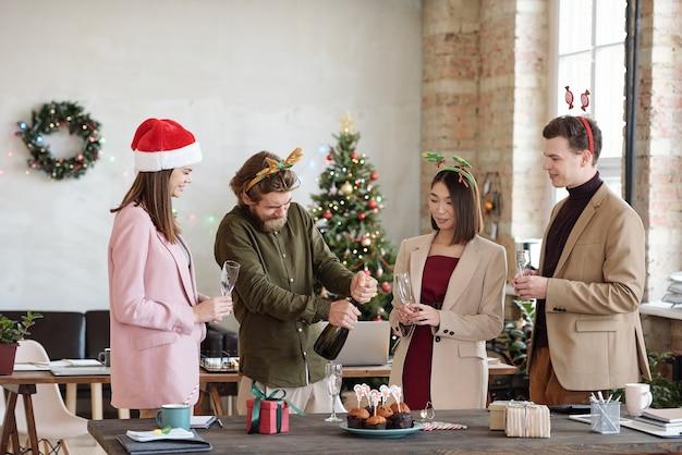 수염 난 남자가 샴페인 병을 여는 것을 기다리는 동안 피리를 들고 크리스마스 머리띠에 젊은 친절한 사무실 관리자 그룹