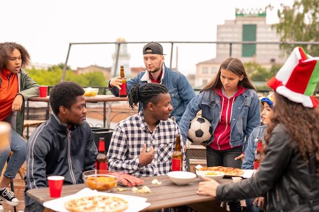 スナック、ウォッチ、今後の試合やゲームの議論のために集まった若いフレンドリーなスポーツファンのグループ