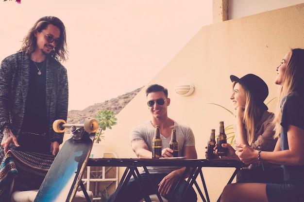 陽気な人々の若い友人のグループは、ビールと楽しみを持って自宅で屋外のレジャー活動を一緒に楽しんでいます