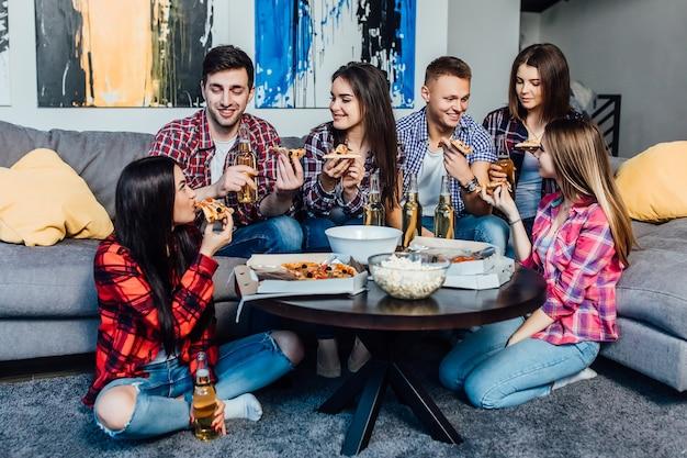 피자를 먹는 젊은 친구들의 그룹입니다. 홈 파티입니다. 패스트 푸드 개념입니다.