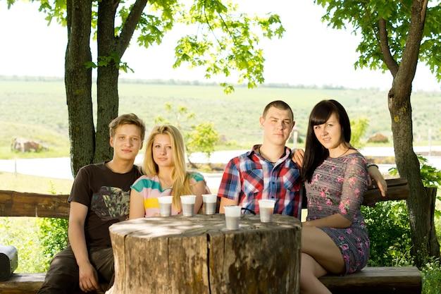 若い友人のグループは、木の切り株のテーブルの周りの素朴な木製のベンチに屋外で座って飲み物を楽しんでいます