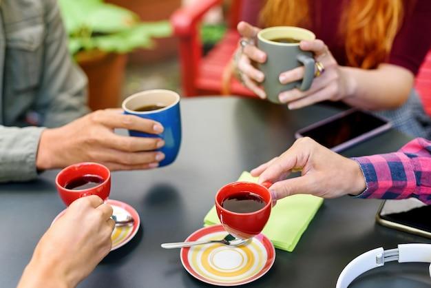 머그와 블랙 커피 한 잔을 들고 테이블 주위에 앉아 손을 가까이에서 함께 커피 휴식을 즐기는 젊은 친구들