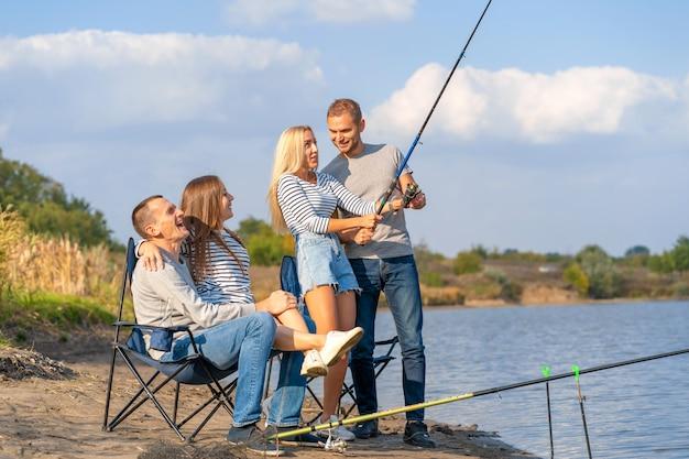 Группа молодых друзей, рыбалка на пирсе у озера