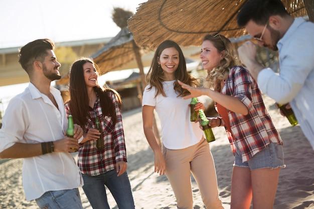해변에서 웃고 맥주를 마시는 젊은 친구들