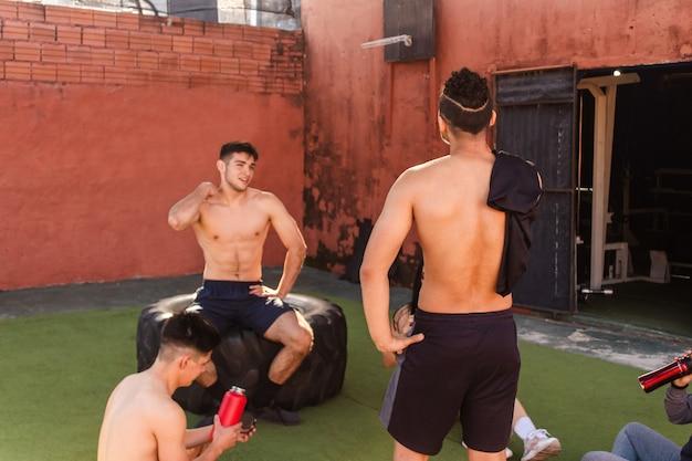 Группа молодых друзей отдыхает, болтает после тренировки во дворе спортзала.