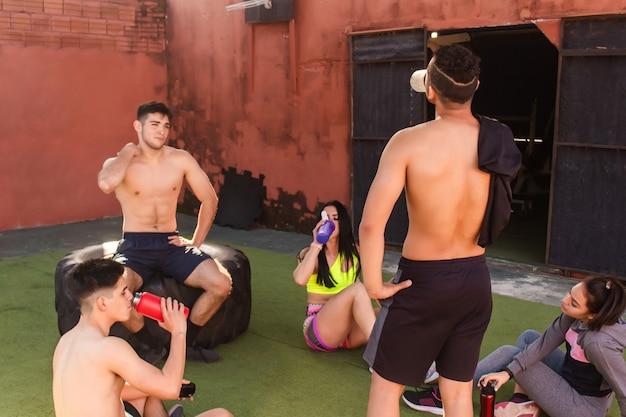 Группа молодых друзей отдыхает, пьет воду, болтает после тренировки во дворе спортзала.