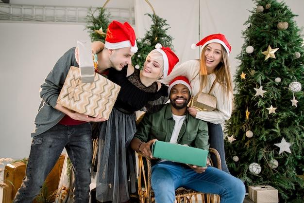 크리스마스 선물을 교환하는 크리스마스 트리 옆에 앉아 젊은 친구의 그룹