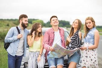 Группа молодых друзей, стоящих перед автомобилем на открытом воздухе