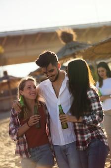 해변에서 이야기하고 맥주를 마시는 젊은 친구들의 그룹