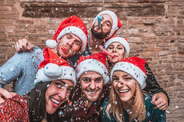 サンタの帽子をかぶってパーティーで楽しんで、写真のポーズをとる若い友人のグループ-大晦日のパーティーでパーティーの笛を吹く幸せな若者-紙吹雪が空中に落ちる