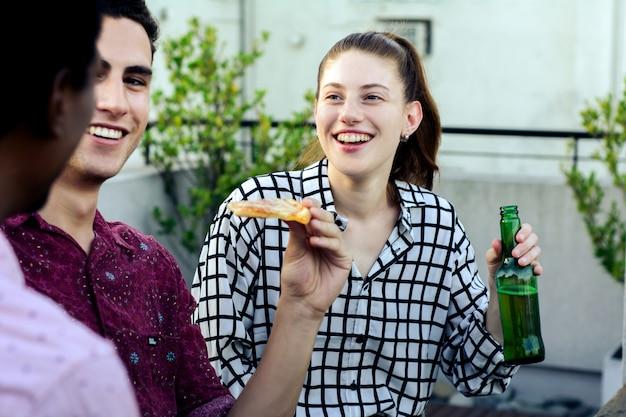 ピザと飲み物のボトルを持つ若い友人のグループ